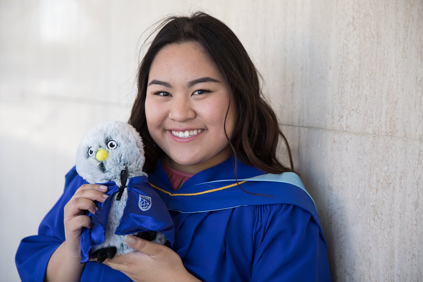 Female NAIT student is wearing blue graduation gown and holding a stuffed Ook while smiling at the camera